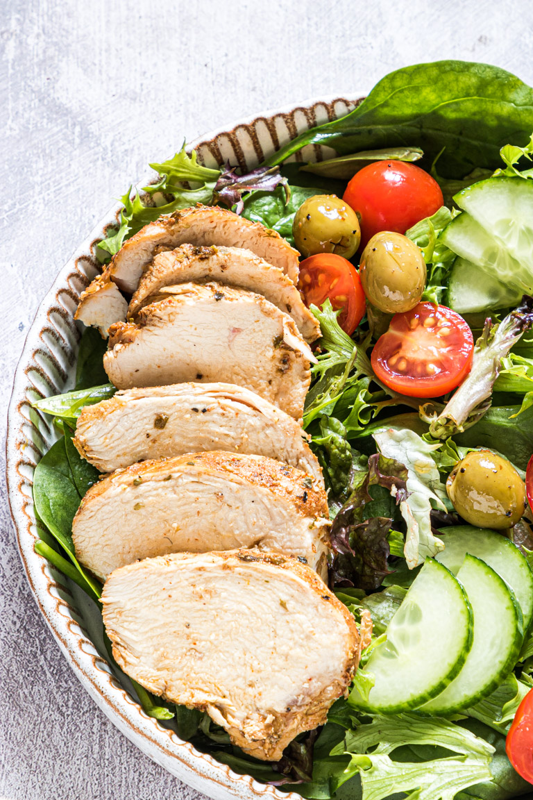 close up view of sliced chicken breast and a green salad served on a plate
