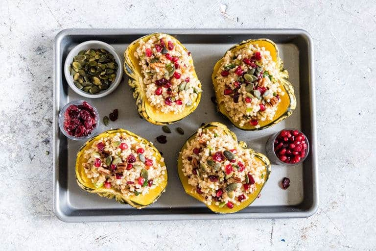 Completed Instant Pot Stuffed Squash halves placed on a baking sheet alongside small dishes of cranberries, pumpkin seeds and pomegranate seeds