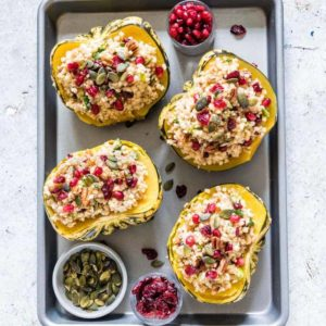 Four servings of Instant Pot Stuffed Squash on a baking sheet alongside small bowls of pumpkin seeds, cranberries, and pomegranate seeds