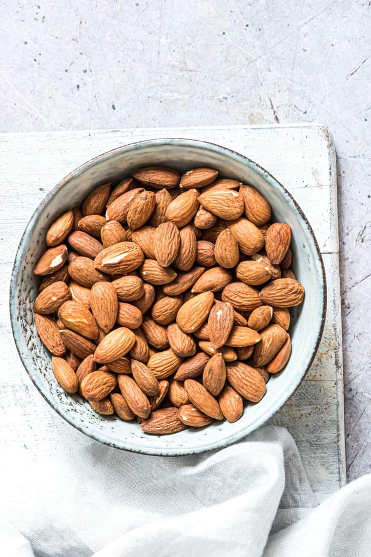 top down view of a blue bowl full of air fryer roasted almonds