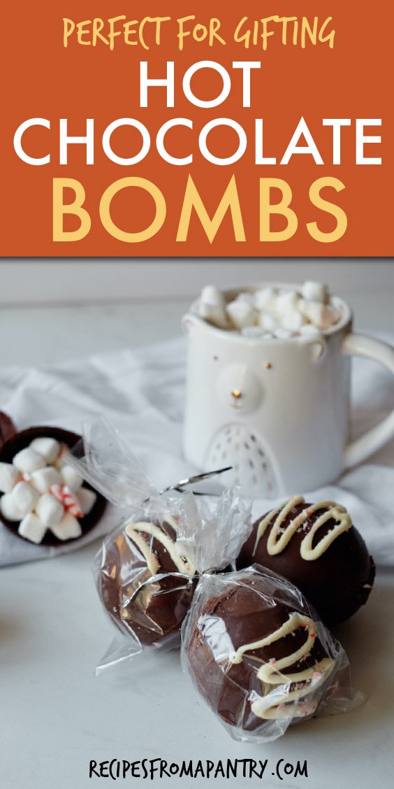hot chocolate bombs wrapped in cellophane in front of a mug