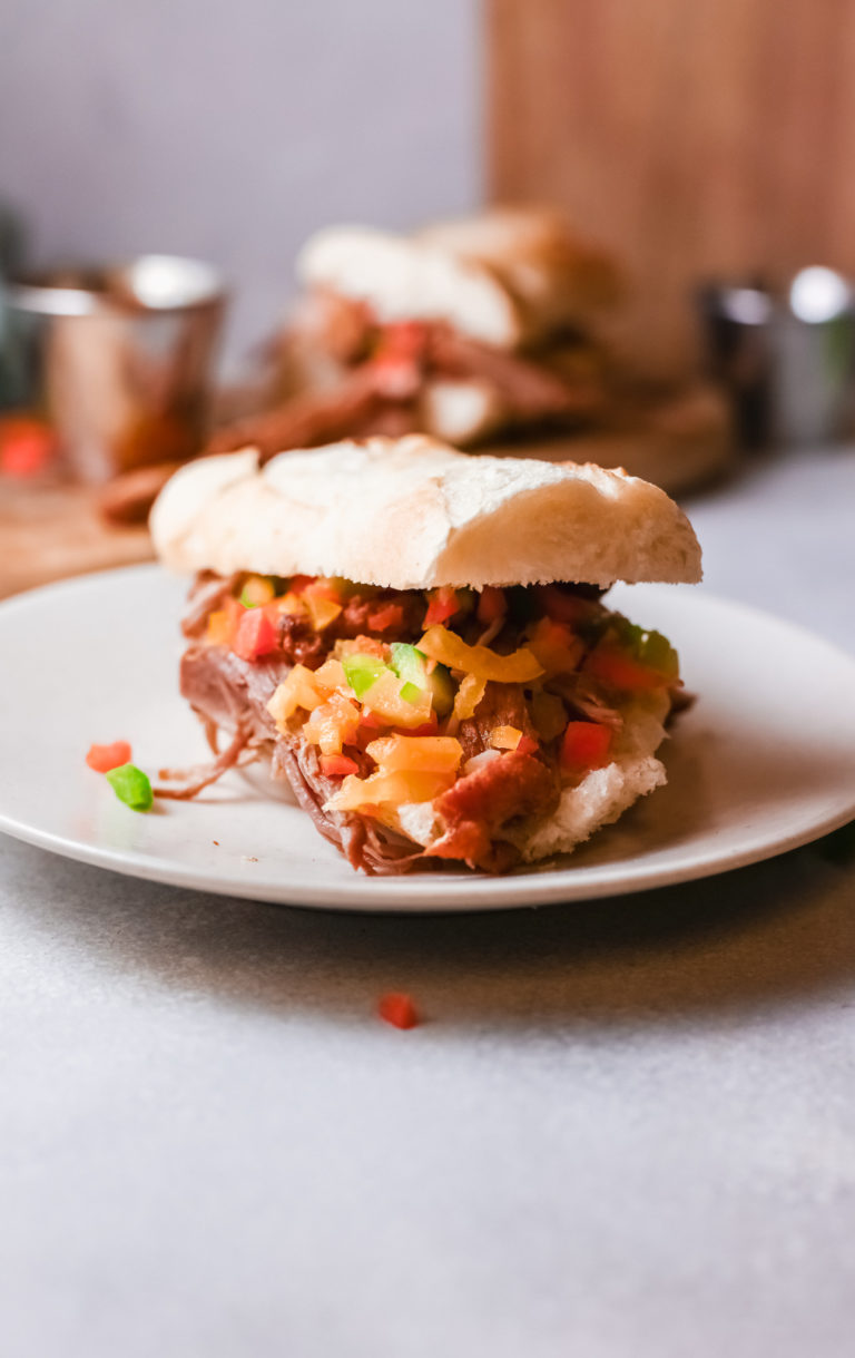 a completed italian beef sandwich served on a white plate