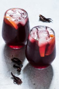 two glasses of Jamaican Sorrel Drink next to dried hibiscus.