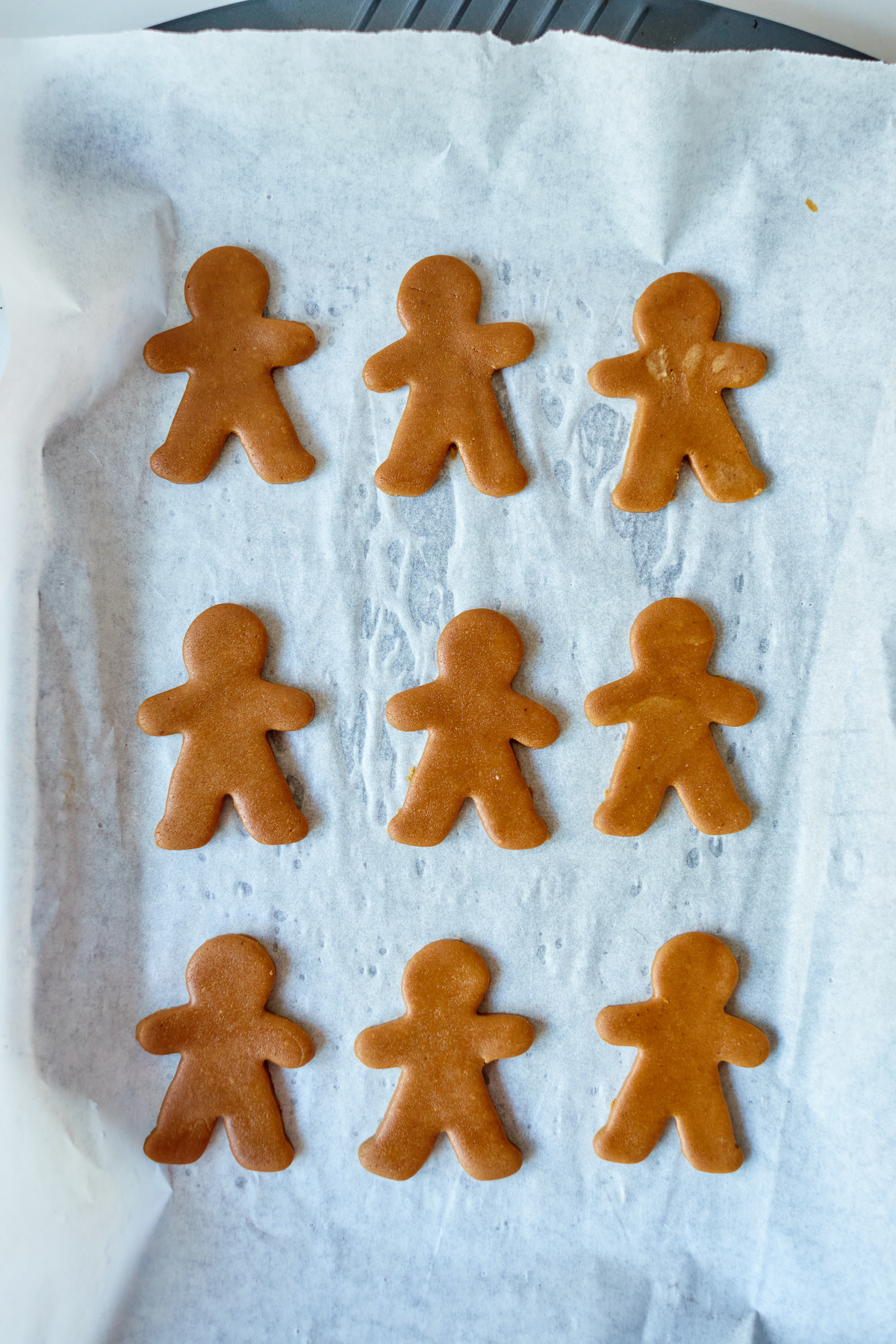 top down view of gingerbread man cookies on a baking tray