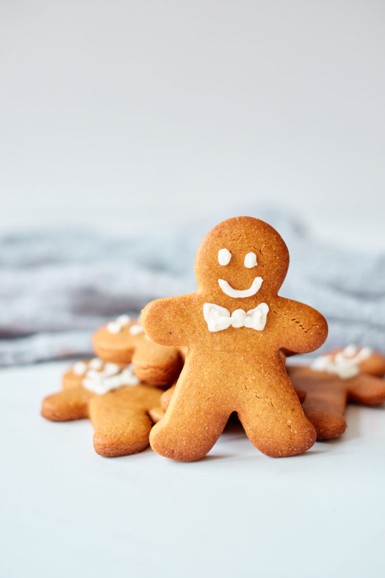 one finished gingerbread man propped up against a stack of cookies