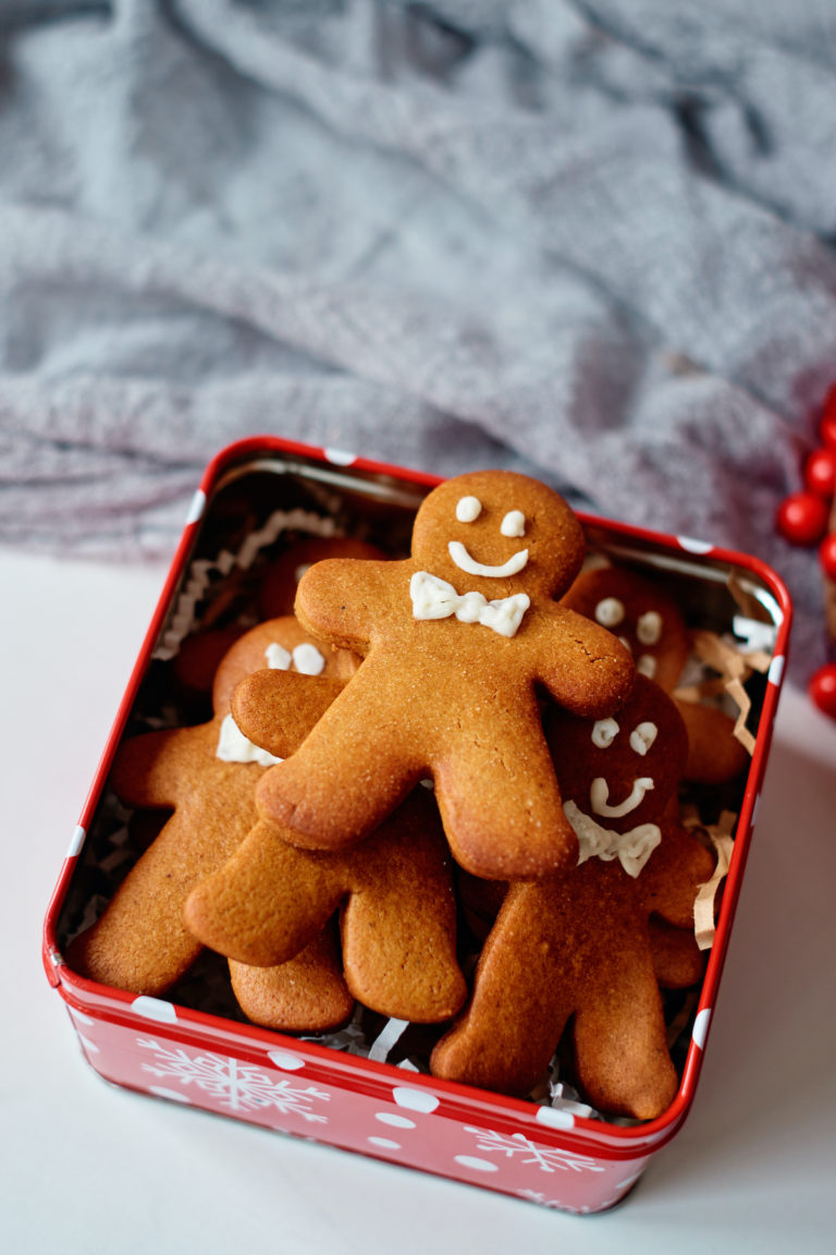 decorated gingerbread man cookies packaged in a red cookie tin