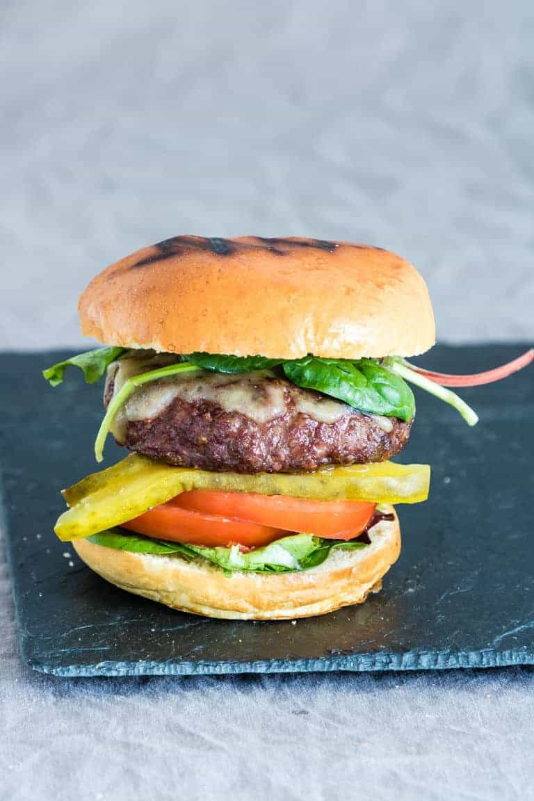 air fryer hamburgers - a burger in a bun with lettuce and tomato and a bun