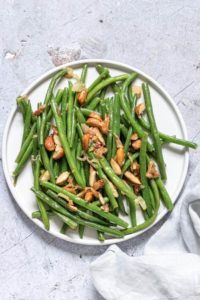 Green Beans Almondine served on a white plate with a cloth napkin
