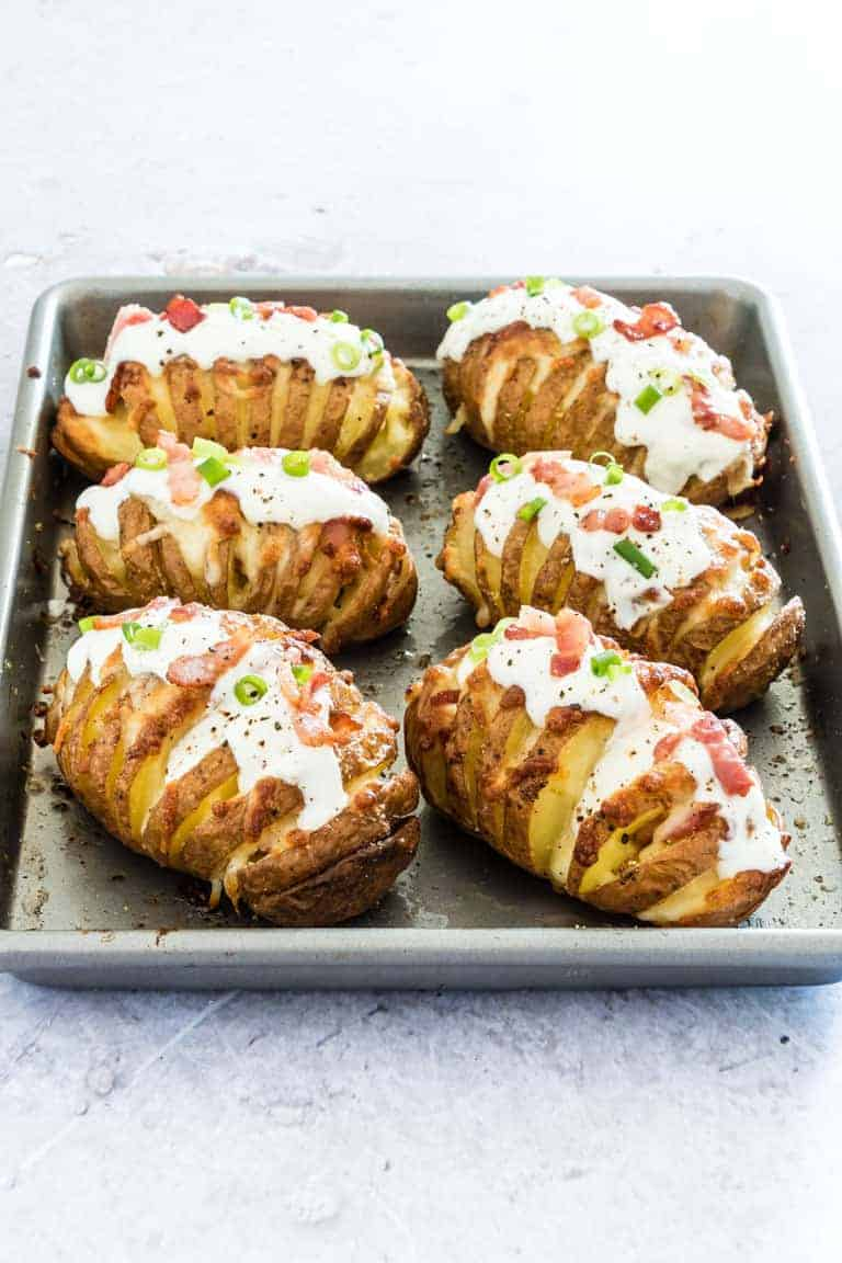 Six Loaded Hasselback Potatoes topped with sour cream, spring onions and bacon lined up on a baking sheet and ready for serving