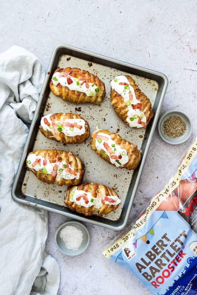 Top-down view of six Loaded Hasselback Potatoes on a baking sheet placed next to a package of Albert Bartlett Rooster Potatoes