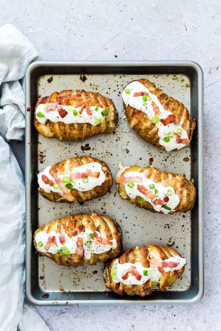 Close-up view of the completed Loaded Hasselback Potatoes set on a baking sheet and ready to be served