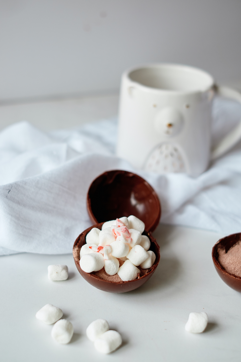an open chocolate bomb with marshmallows spilling out