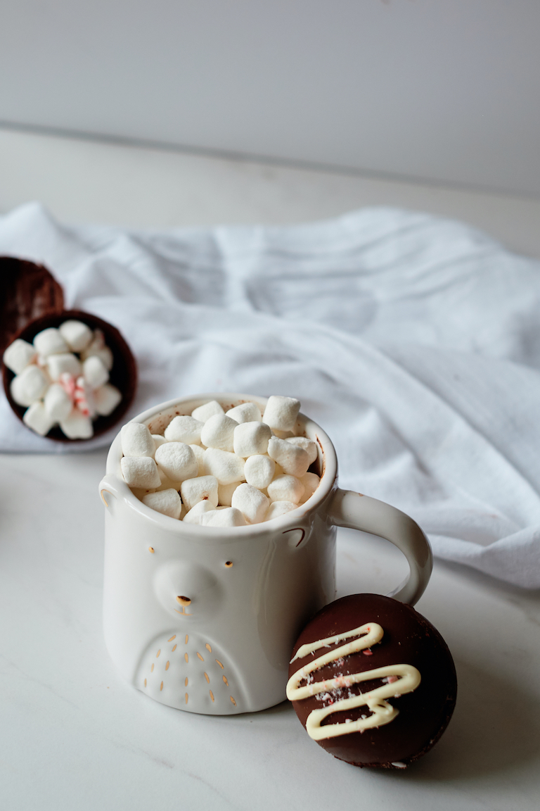 a mug of hot cocoa next to a chocolate bomb