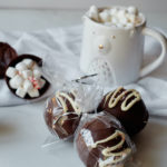 three chocolate bombs packages as edible gift ands placed in front of a mug of hot chocolate