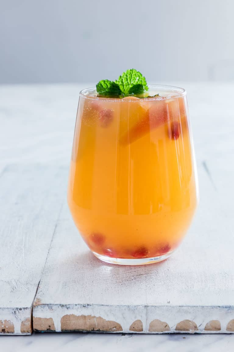 peach bellini in a glass with garnishes