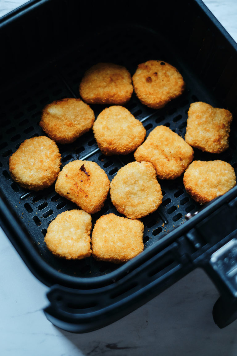 top down view of cooked frozen chicken nuggets inside the air fryer basket