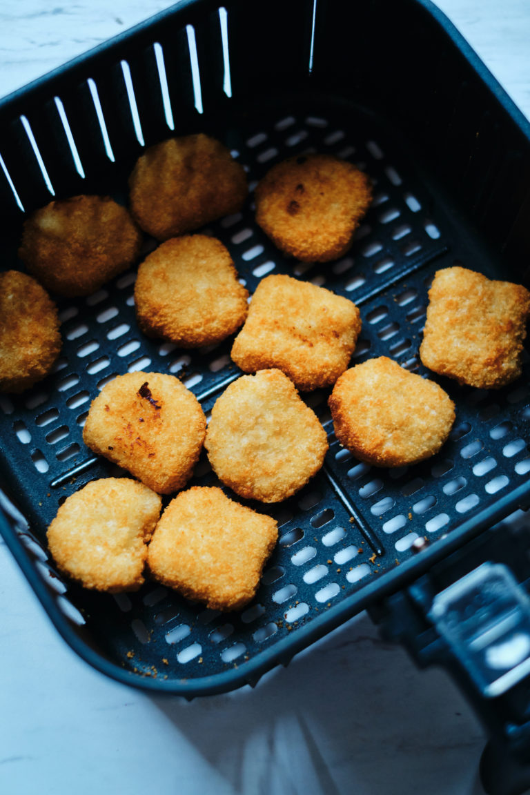 top down view of the frozen chicken nuggets inside the air fryer basket