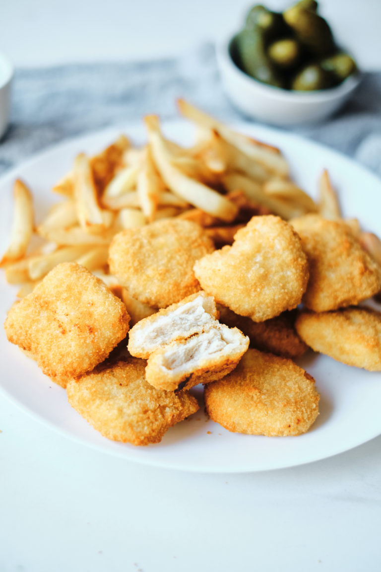 air fryer frozen chicken nuggets on a white plate with a side of fries