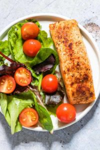 The finished Air Fryer Salmon served on a white plate with a green salad