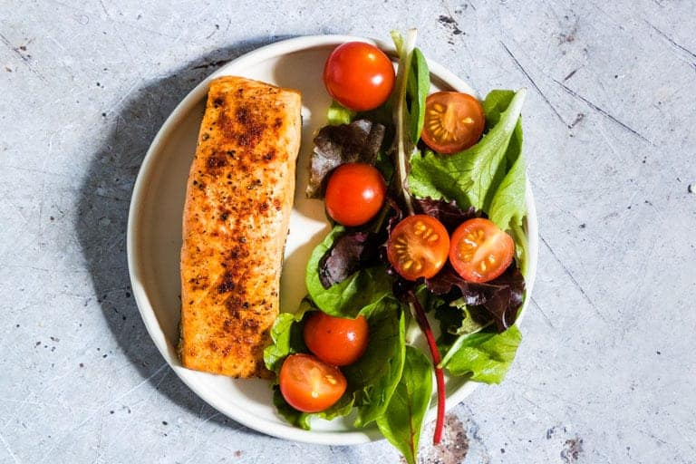 Air Fryer Salmon served with a green salad on a white plate