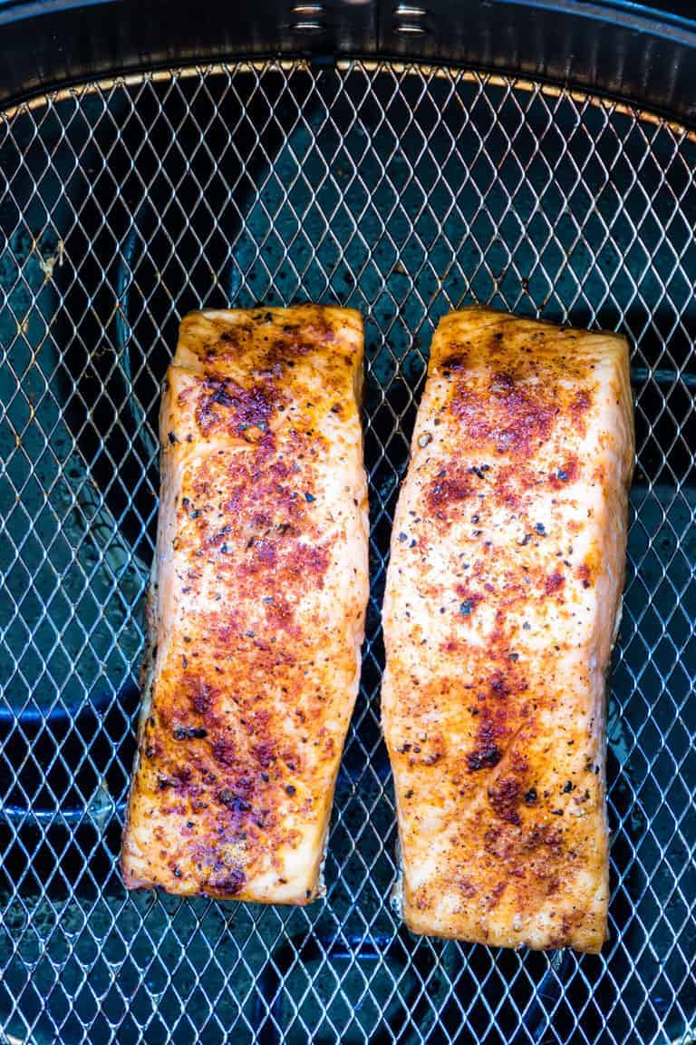 Two cooked Air Fryer Salmon fillets inside the air fryer basket