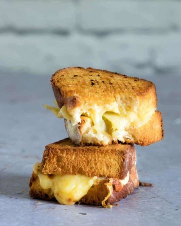 Two halves of the completed Air Fryer Grilled Cheese sandwich stacked and ready to serve