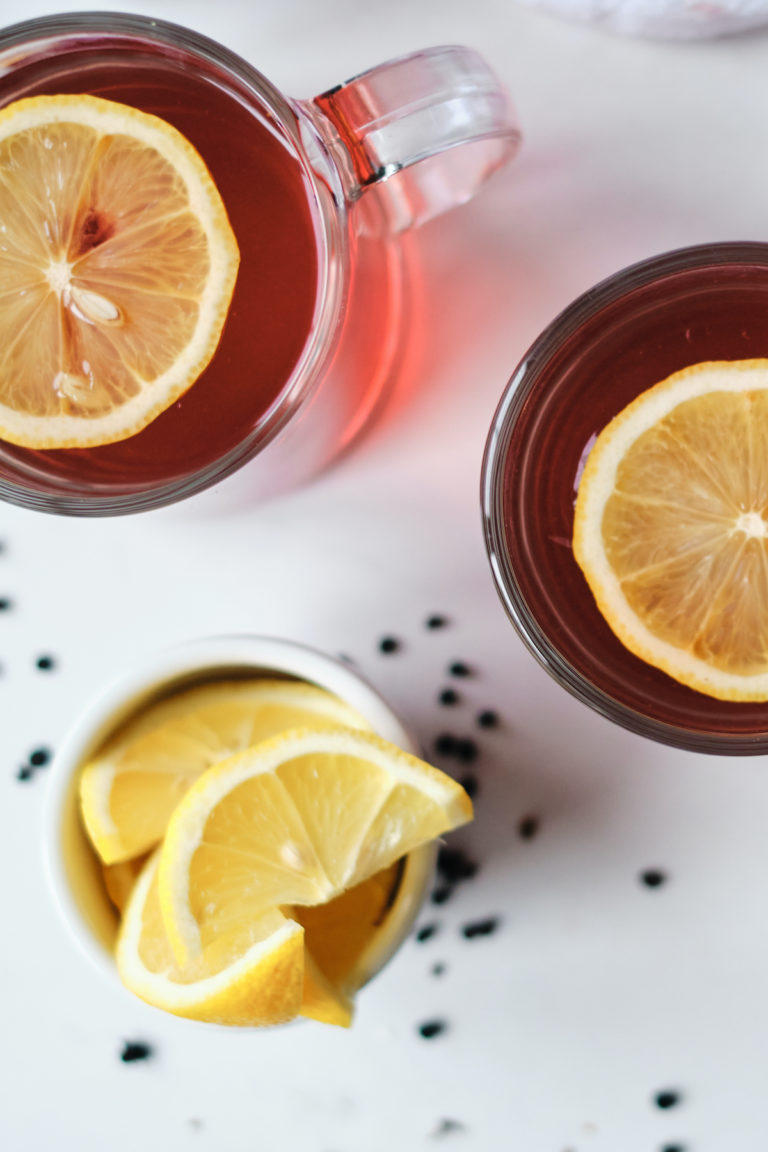 top down view of two glass mugs filled with elderberry tea and lemon