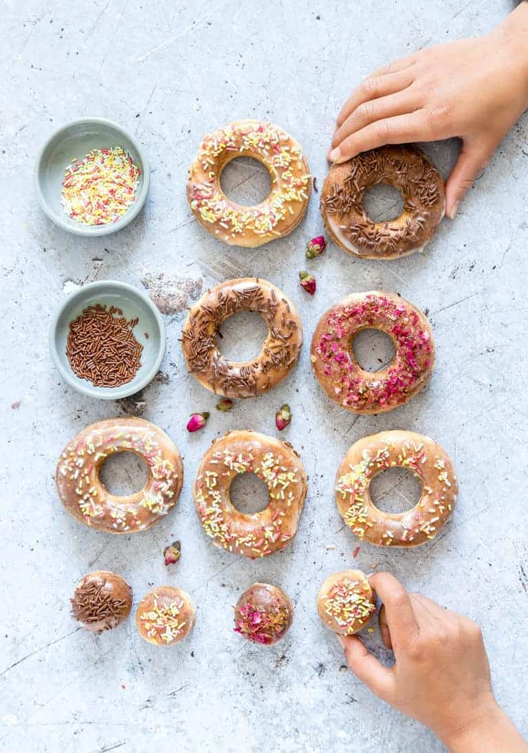 hands reaching for air fryer donuts with sprinkles