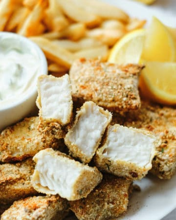 close up view of a serving of fish sticks on a white plate with lemon wedges and tartar sauce