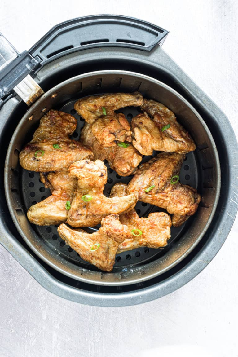 top down view of cooked chicken wings inside the air fryer basket