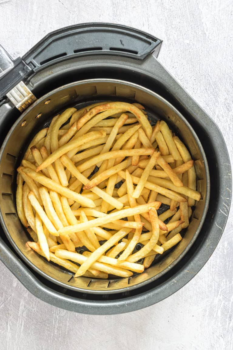 the cooked frozen french fries inside the air fryer basket