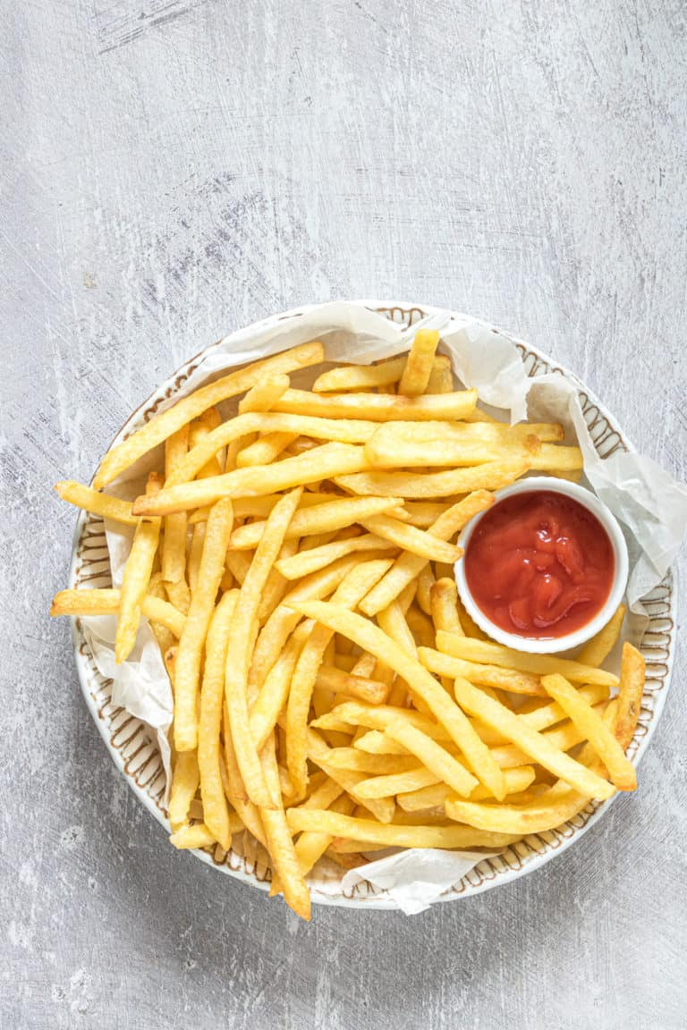 top down view of the finished air fryer frozen french fries served on a plate with a small bowl of ketchup