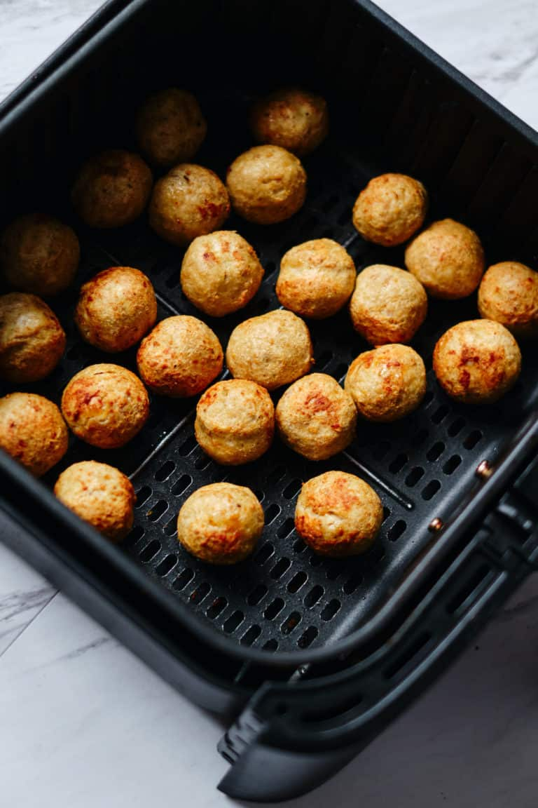 the cooked frozen meatballs inside the air fryer basket