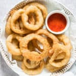the finished air fryer frozen onion rings served on a ceramic plate with a small bowl of dipping sauce
