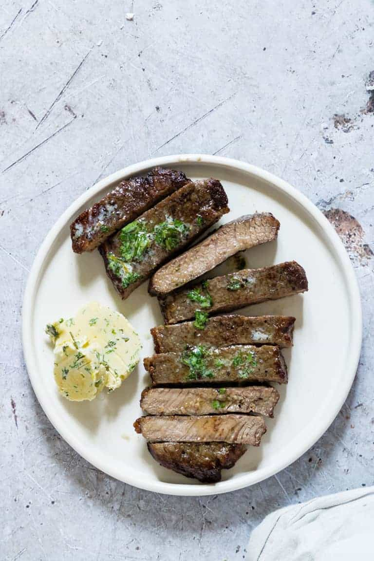 close of up of air fryer steak sliced on a plate with herb butter