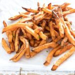 Completed Air Fryer Sweet Potato Fries on white parchment paper and ready to be served