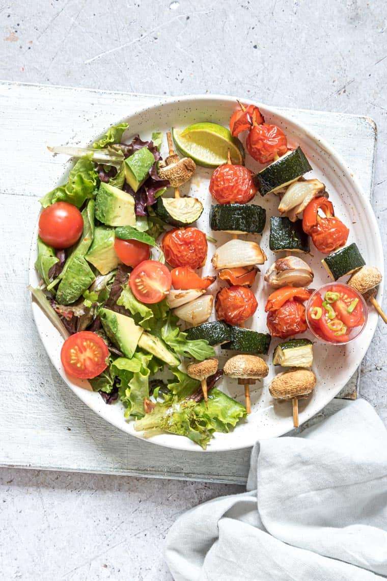air fryer vegetable kabobs on a white plate with a green salad