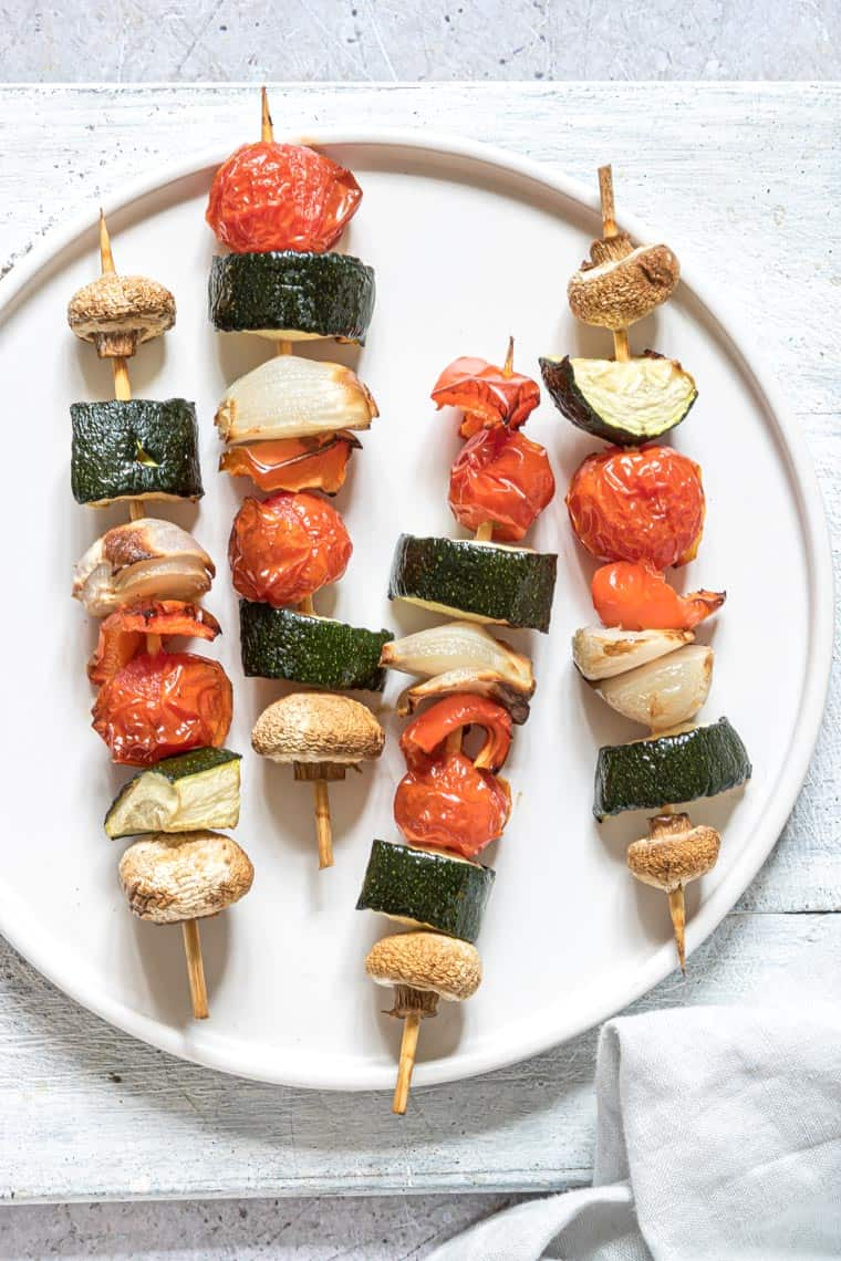 close up of four air fryer vegetable kabobs on a white dinner plate