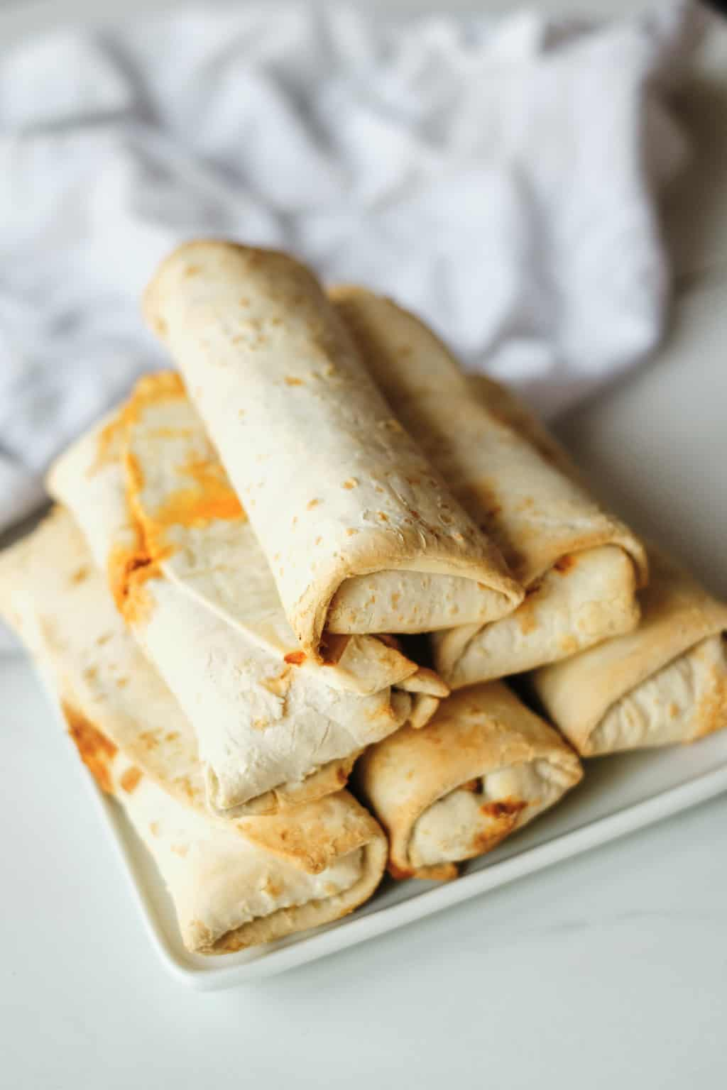 cooked frozen burrito in air fryer stacked on a white plate