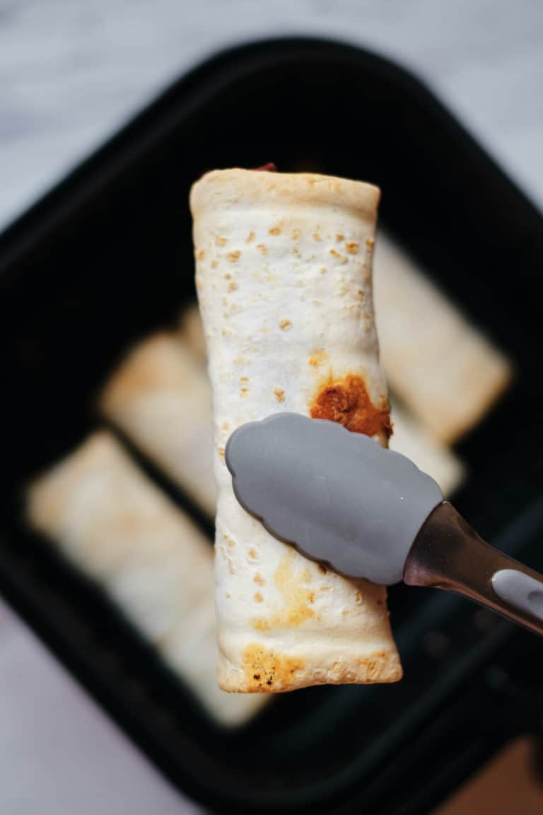 one cooked frozen burrito being removed from the air fryer with tongs