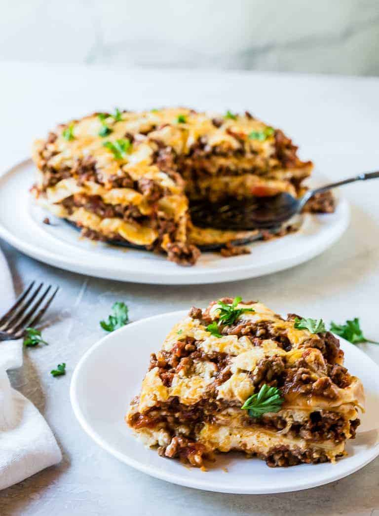 one serving of Instant Pot Lasagna cut from the whole dish and served on a white plate with a parsley garnish