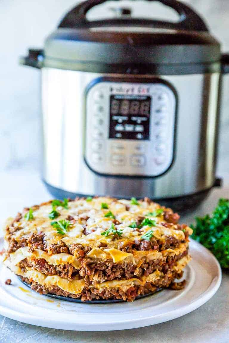 Completed Instant Pot Lasagna served on a white plate and sitting in front of the Instant Pot