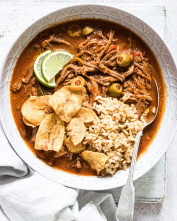top down view of a bowl filled with ropa vieja, plantains and rice