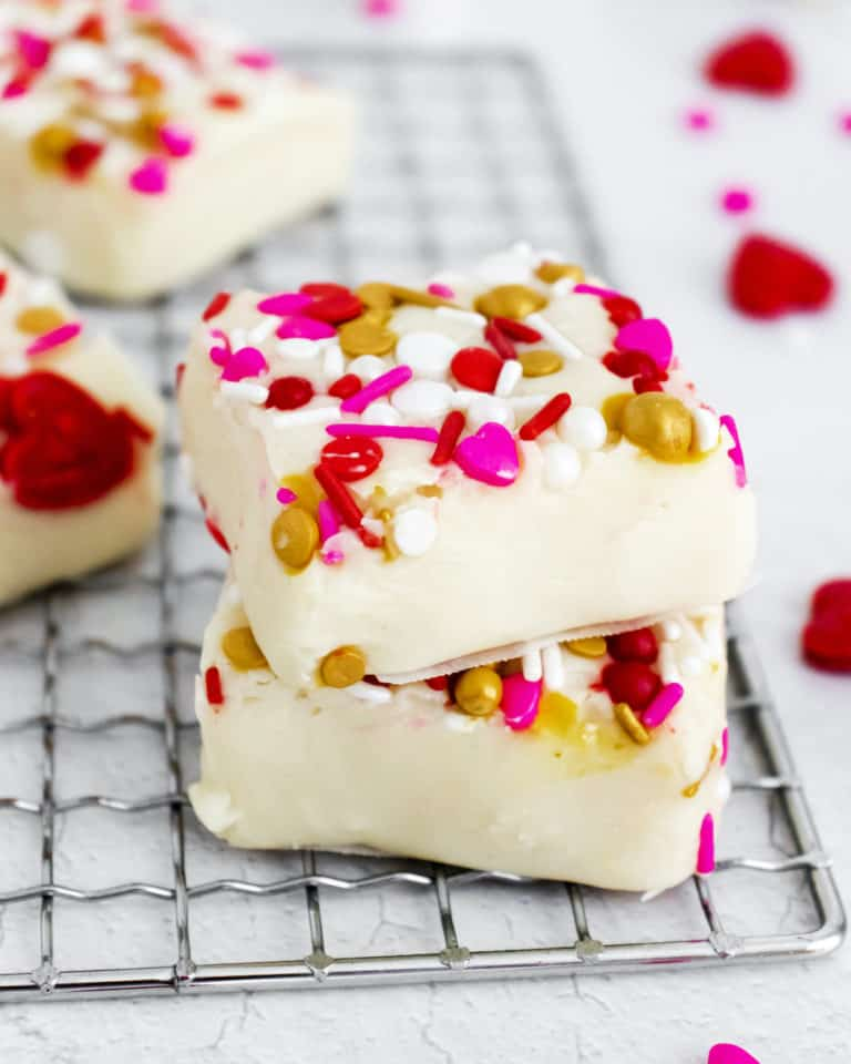close up view of two pieces of white chocolate fudge stacked vertically