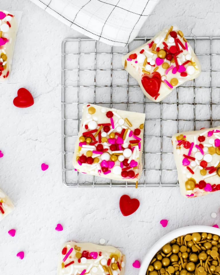 top down view of pieces of white fudge on a baking rack next to dishes of prinkles