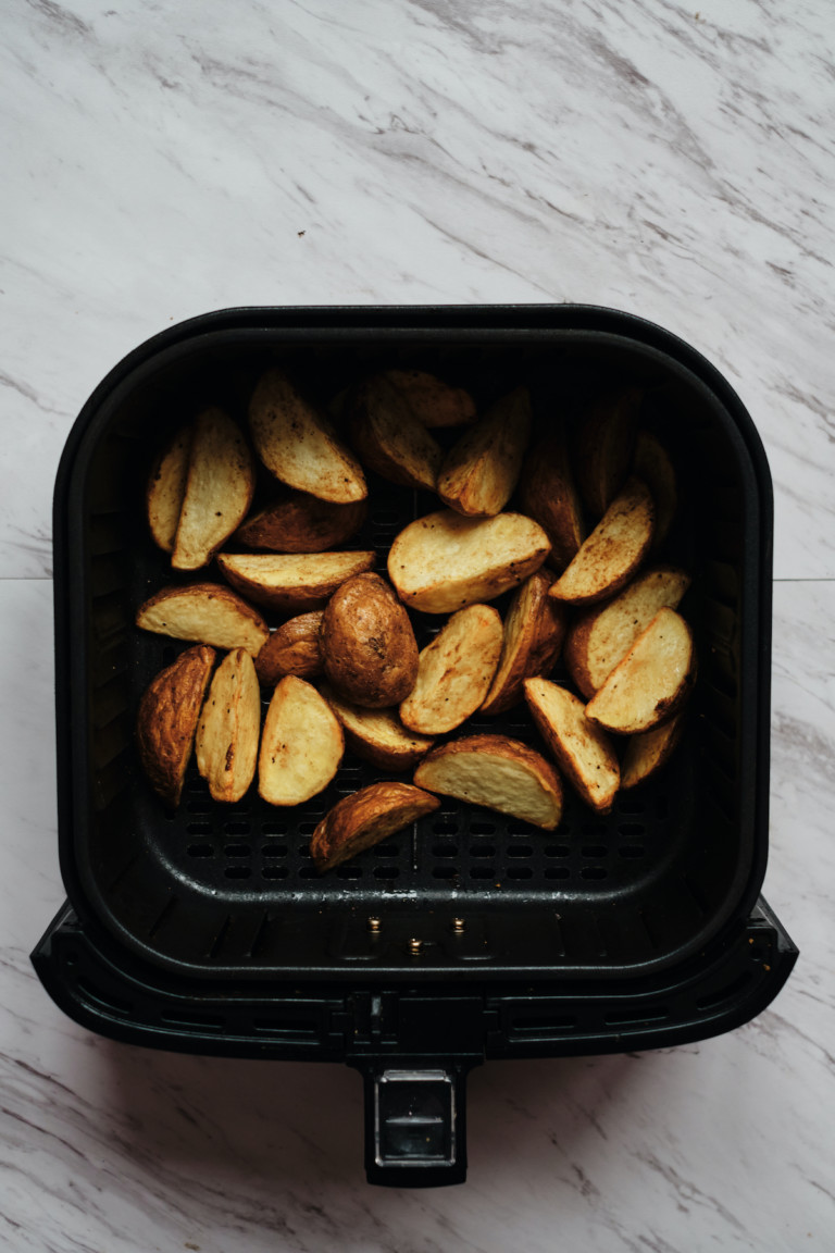 the cooked potato wedges inside the air fryer basket