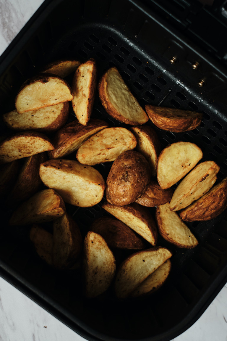 the finished potato wedges inside the air fryer basket