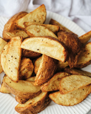 close up view of the completed air fryer potato wedges served on a white plate