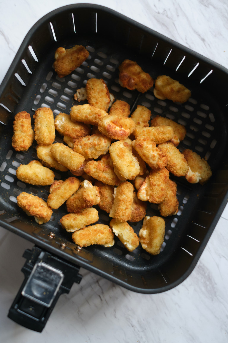 top down view of the completed frozen mozzarella sticks inside the air fryer basket