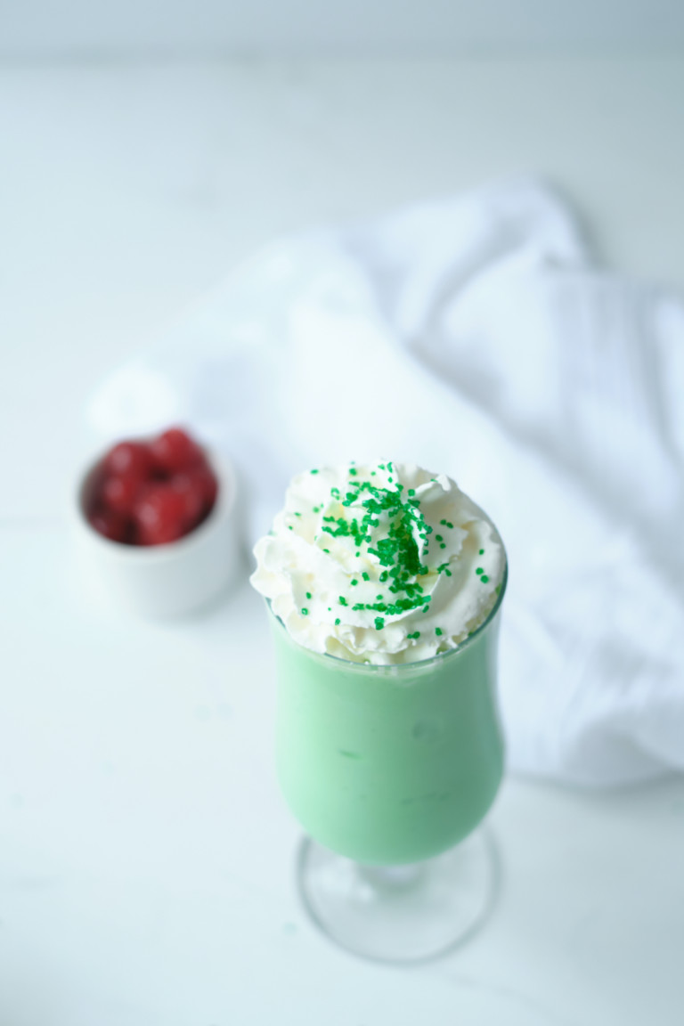 top down view of one shamrock shake topped with whipped cream and sprinkles